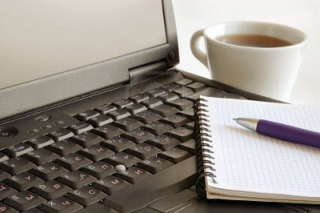 Spiral-notebook-pen-and-cup-of-coffee-on-laptop-keyboard